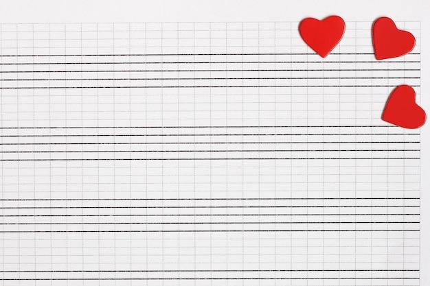 Cuori di carta rossa giacciono su un taccuino musicale pulito. il concetto di musica e amore.