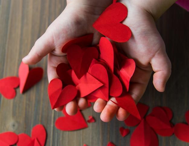 Cuori di carta rossa nelle mani del bambino. l'amore firma dentro il giorno di biglietti di s. valentino.