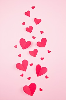 Cuori di carta su sfondo rosa pastello. sfondo astratto con forme di taglio carta. sainte valentine, festa della mamma, biglietti d'auguri di compleanno, invito, celebrazione concetto