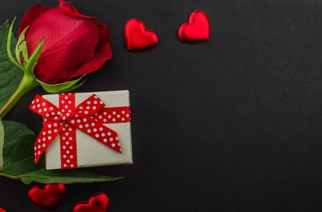 Cuori di giorno di biglietti di s. valentino e della rosa rossa su legno. copia spazio per il testo