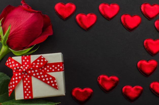 Cuori di giorno di biglietti di s. valentino e di rosa rossa su legno. copia spazio per il testo