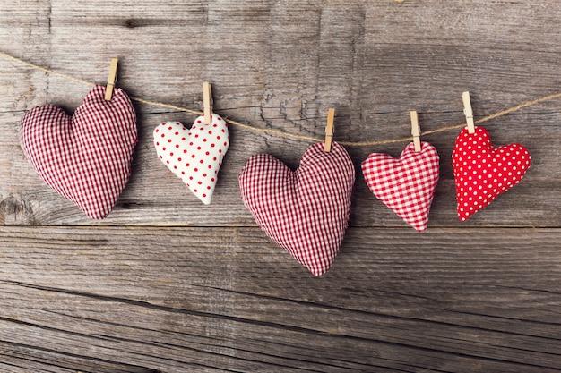 Cuori di giorno di san valentino di tessili su legno