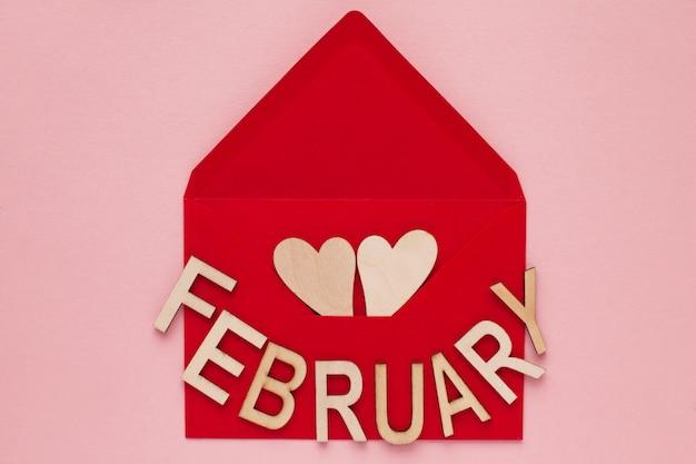 Cuori di legno e la parola dalle lettere febbraio in una busta di carta rossa
