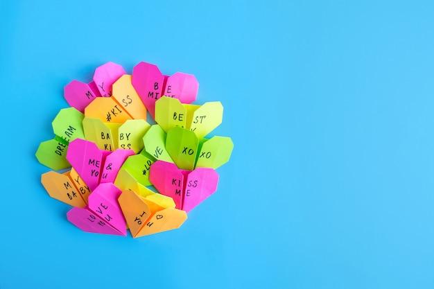 Cuori di origami di carta brillante multicolore con testo amore