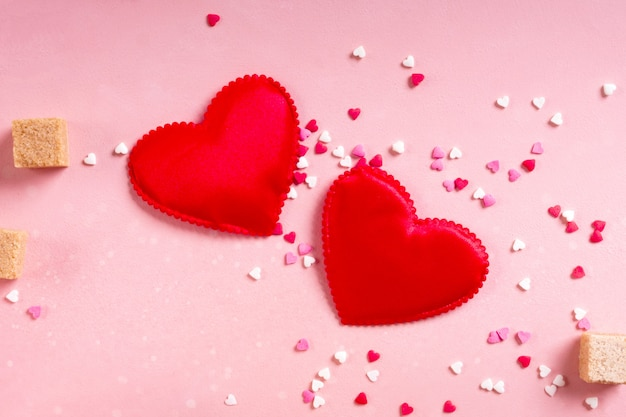 Cuori di tessuto rosso, zollette di zucchero, coriandoli su sfondo rosa. san valentino 14 febbraio ama il concetto minimo