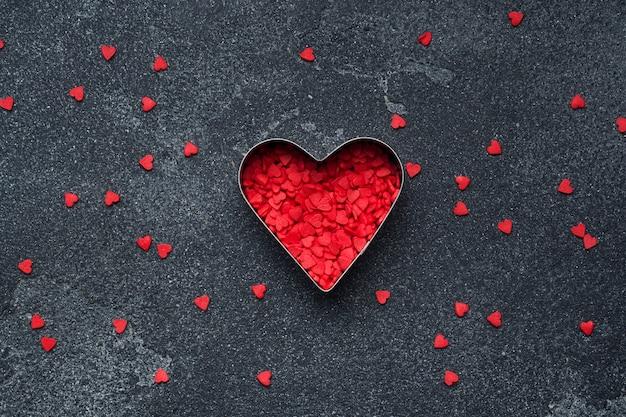 Cuori di zucchero rosso su uno sfondo scuro.