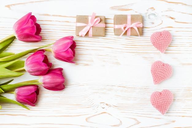 Cuori lavorati a maglia, regali con un nastro rosa e un mazzo di tulipani su un legno bianco, vista dall'alto