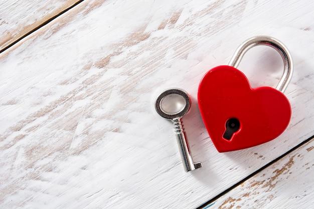Cuori rossi del lucchetto con la chiave su legno bianco., copyspace