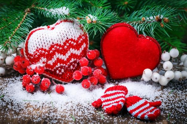 Cuori rossi della decorazione di giorno di biglietti di s. valentino su neve. messa a fuoco selettiva,