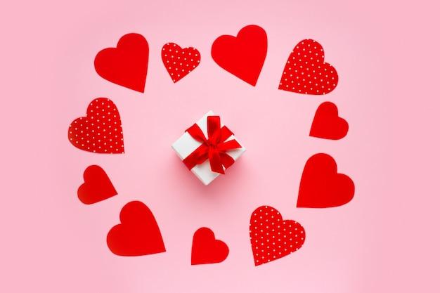 Cuori rossi di carta intorno ad un contenitore di regalo sul rosa. buon san valentino concetto.