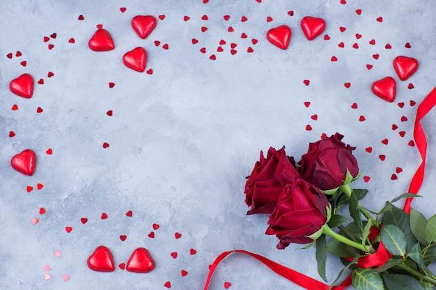 Cuori rossi di diverse dimensioni e tre rose rosse legate con un nastro su uno sfondo grigio