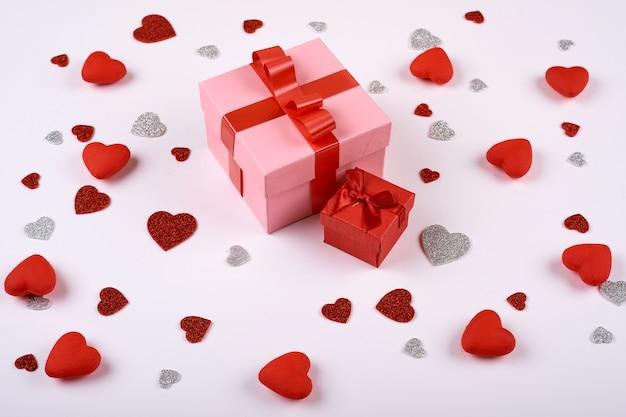 Cuori rossi e argento su uno sfondo bianco intorno a un grande regalo. san valentino.
