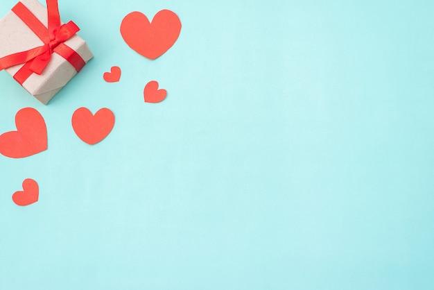 Cuori rossi e bianchi del contenitore di regalo, su fondo pastello blu. san valentino o concetto di cerimonia di nozze