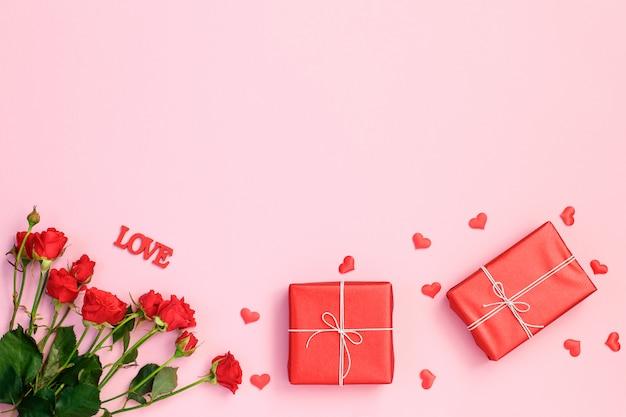 Cuori rossi, rosa e scatola regalo su sfondo rosa