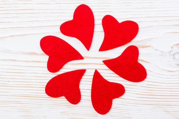 Cuori rossi su un fondo di legno bianco