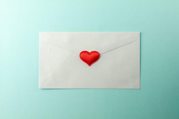 Cuori rossi timbrati in busta bianca su sfondo blu carta