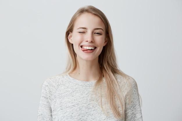 Cupa giovane donna bionda con i capelli tinti vestita casualmente facce, sbattendo le palpebre, sporgendo la lingua. donna positiva divertendosi al chiuso