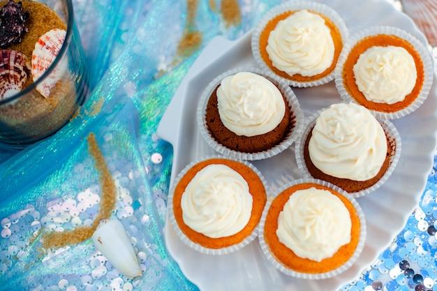 Cupcack alla vaniglia con crema bianca sul piatto a forma di conchiglia