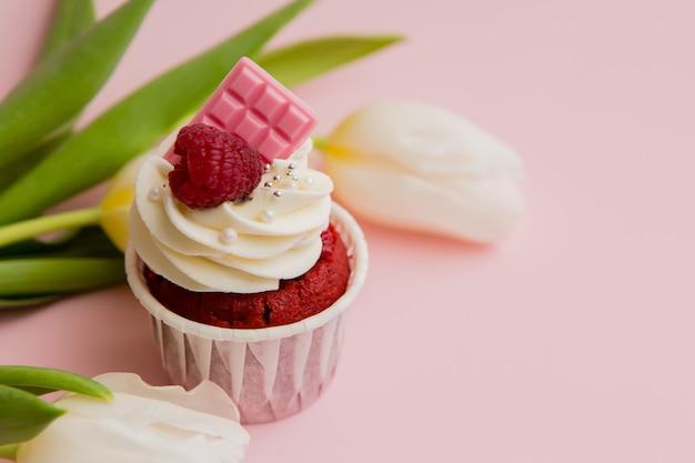 Cupcake al cioccolato e tulipani bianchi su uno spazio rosa