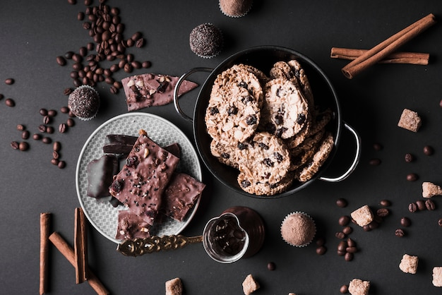 Cupcake; biscotti e tartufi al cioccolato fatti con chicchi di caffè e cioccolato su sfondo nero