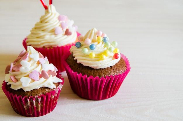 Cupcake celebrativo per san valentino e buon compleanno sul tavolo di legno bianco con cuori. dai amore in vacanza