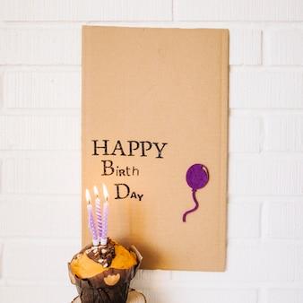 Cupcake con candele vicino cartone con saluto