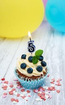 Cupcake con una candela di numero cinque