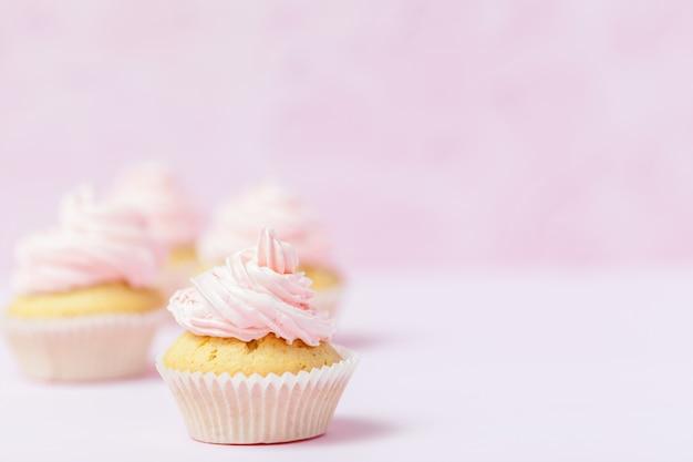 Cupcake decorato con buttercream rosa su sfondo rosa pastello. dolce bella torta