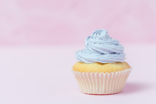 Cupcake decorato con buttercream viola su sfondo rosa pastello.