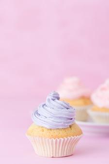 Cupcake decorato con crema di burro rosa e viola su sfondo rosa pastello.