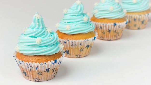 Cupcake decorato con fiocchi di neve di zucchero e crema blu. cupcakes invernali di natale