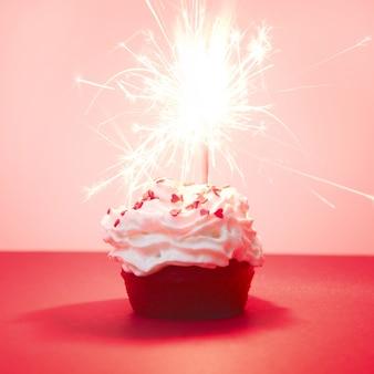 Cupcake di velluto rosso con luci bengal su rosso.