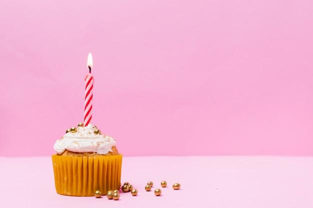 Cupcake dolce con candela accesa su di esso