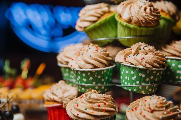 Cupcakes al cioccolato appena fatti, decorati con panna e palline colorate