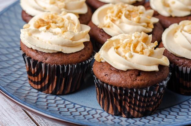 Cupcakes al cioccolato con crema al caramello decorato con arachidi schiacciate su sfondo blu.