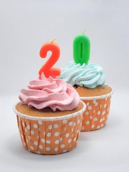 Cupcakes al cioccolato con il 20 ° compleanno di candele o il concetto di anniversario