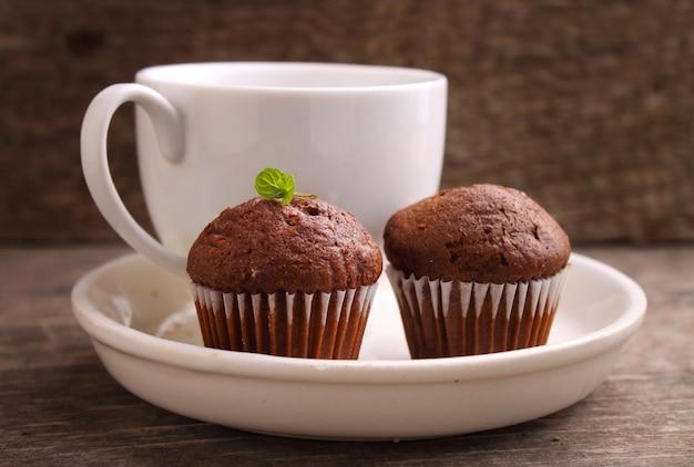 Cupcakes al cioccolato con una tazza di tè su un piatto bianco