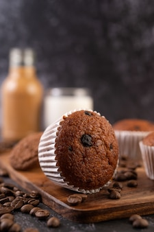 Cupcakes alla banana che vengono posizionati su un piatto di legno con chicchi di caffè.