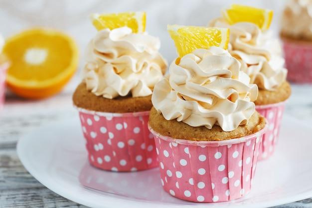 Cupcakes alla vaniglia con un tappo di crema su tablein in legno bianco