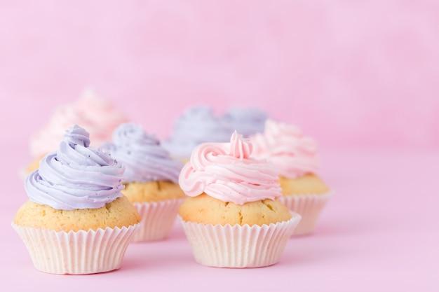 Cupcakes con buttercream viola e rosa in piedi su sfondo rosa pastello.
