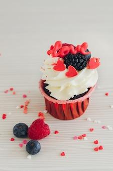 Cupcakes con crema bianca, frutti di bosco freschi e decorazioni