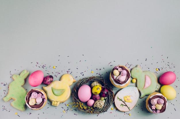 Cupcakes di pasqua, uova dipinte e pane allo zenzero su sfondo grigio
