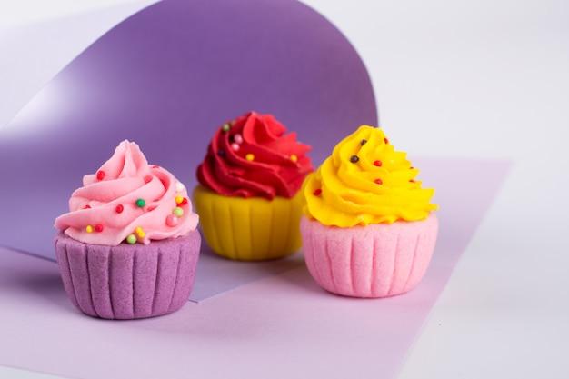 Cupcakes di zucchero multicolore decorativo su sfondo viola chiaro con spruzza