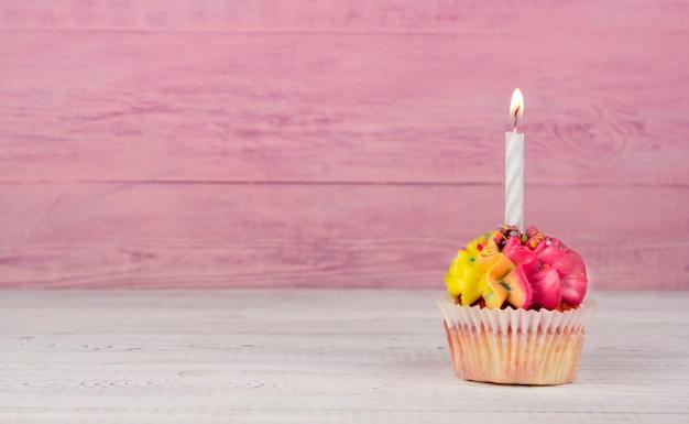 Cupcakes fatti in casa con crema multicolore su uno sfondo rosa copia spazio. crema gialla e rosa