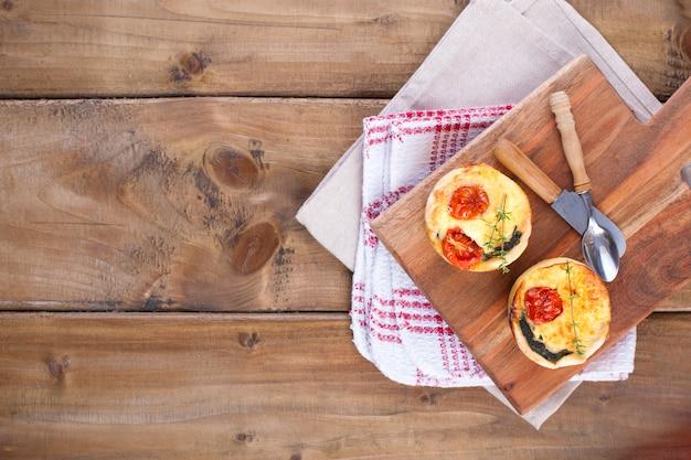 Cupcakes fatti in casa con formaggio e pomodorini su una tavola di legno