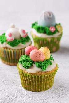 Cupcakes festivi con uova di mastice ed erba su sfondo luminoso. concetto di vacanze di pasqua. copia spazio