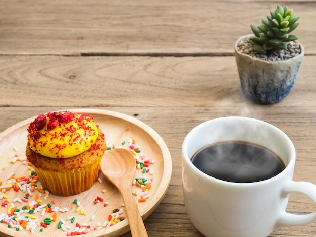 Cupcakes gialli messi su un piatto di legno sferico.