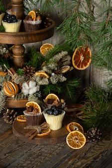 Cupcakes natalizi a base di cioccolato bianco e fondente, decorati con bacche, noci e fette di mandarini.