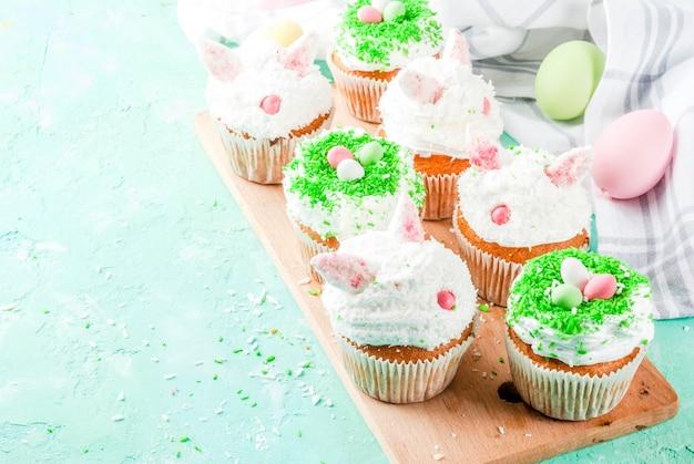 Cupcakes pasquali con orecchie da coniglio e uova di caramella,