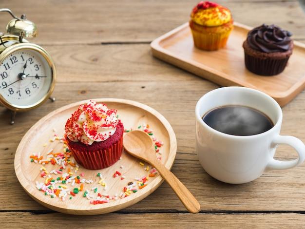 Cupcakes rossi messi su un piatto di legno sferico accanto al cupcake